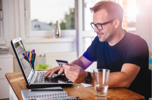 En bild på en man som betalar med kreditkort via datorn.