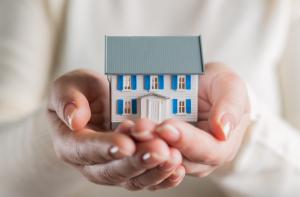 Bild på ett hus i två händer, symboliserar att man tar hand om sitt hus även om man inte kan betala lånet pga. sjukdom t.ex.